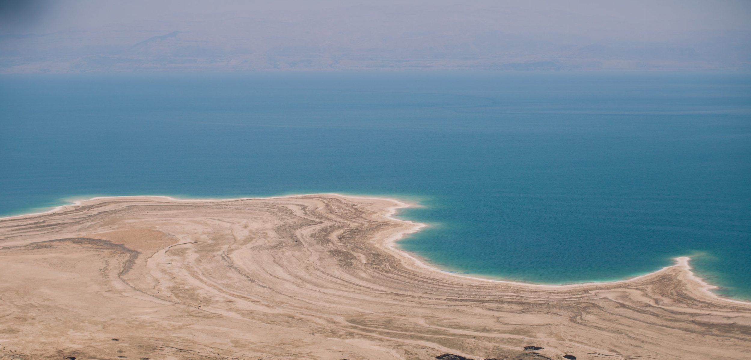 THE DEAD SEA - The Dead Sea shrinks every year, and the ground around it becomes unstable sinkholes, as we could see from the road where I took this landscape shot. Guests enjoy themselves, despite the increasingly long walks to the shoreline.