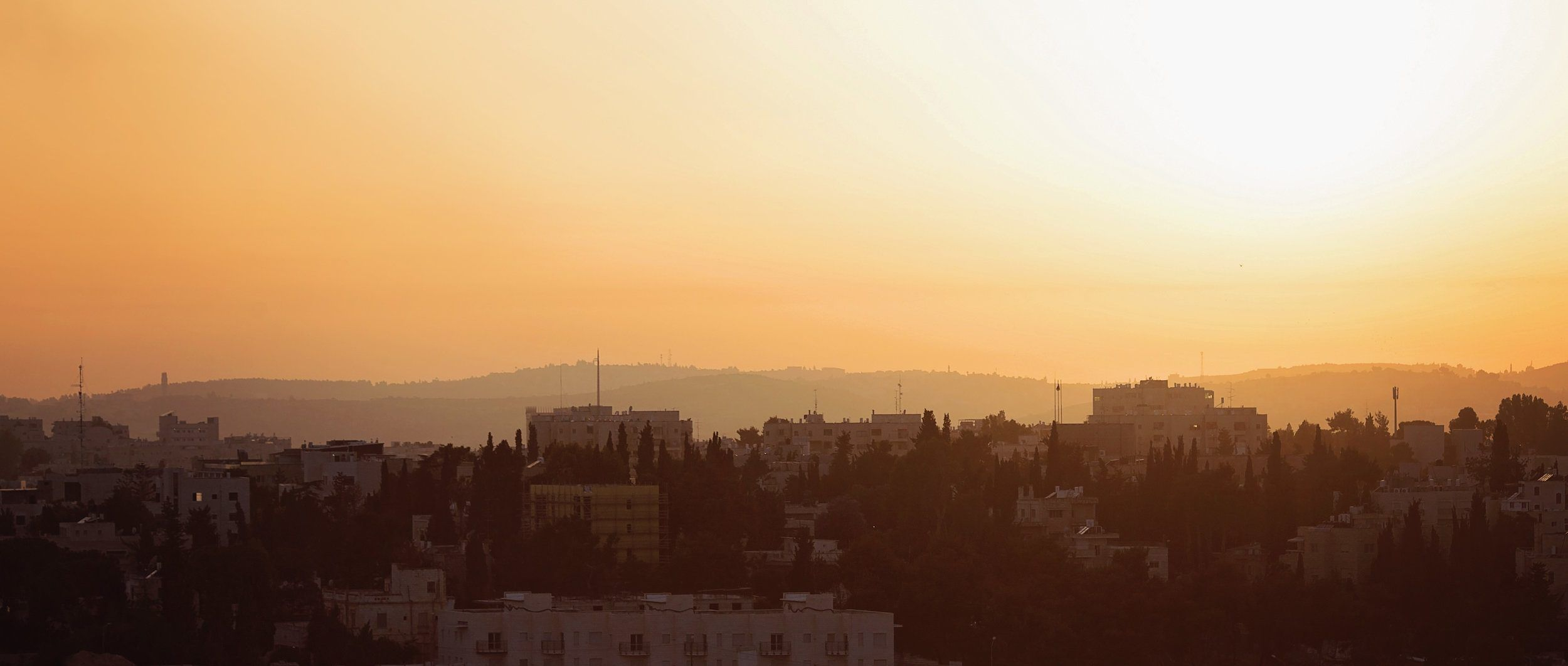 SUNSET IN JERUSALEM - On our first day in Jerusalem, we drove to a lookout to watch the sun set over the city. The haze sent the sun glowing across the desert and bringing life to the stories I'd heard for years and years about all that happened in this city.